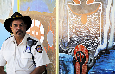 Prison Officer next to murals created by prisoners
